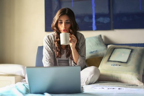 Woman drinking coffee in bed working on her laptop