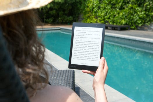 Woman reading eBook by pool